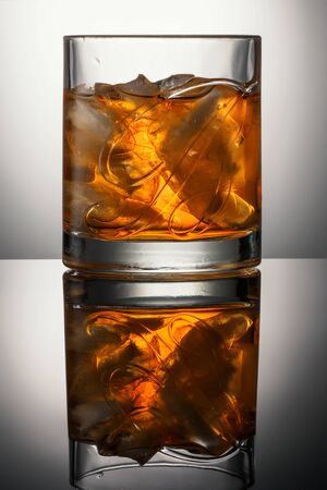 CHELYABINSK, RUSSIA - April 10,2018 Glass of Finest Blended Scotch Whiskey Ballantines Logo with natural ice cubes advertising shot on background with realistic reflection Delicious Scotch Whisky Ballantines is produced in Dambarton, Scotland by Pernod Ri Editorial
