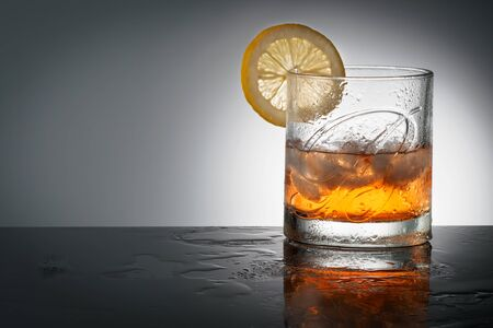 CHELYABINSK, RUSSIA - April 10,2018 Glass of Finest Blended Scotch Whiskey Ballantines Logo with natural ice cubes and a slice of lemon advertising shot on background Delicious Scotch Whisky Ballantines is produced in Dambarton, Scotland by Pernod Ricard