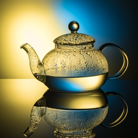 Glass teapot with boiling water and drops of condensation on glass advertising shot on light multy colored background with realistic reflection of gloss reflexes Close-up of macro with copy space.