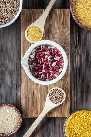 Set Traditional organic vegan ingredient Super Food in Middle East and Asian cooking cereals red lentil lens culinaris rice wheat beans bulgur culinary spoons bowls low key rustic Wabi Sabi lifestyle.