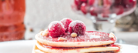 Pancakes homemade cake in stack decorated with berries frozen cherry and pine nut on white plate and  light background low key concept healthy breakfast with mug of flower tea. Stock Photo