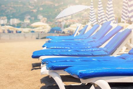 Empty sunbeds with blue mattresses on sandy beach near ocean sea at sunset