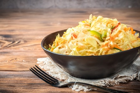 Salad appetizer of fermented vegetables sauerkraut carrots and peppers in bowl with fork on rustic wooden background. Concept trend diet food vegetarian recipes to homemade
