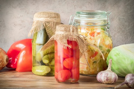 Set of fermented vegetables in jars on wooden rustic table. Cabbage salad sauerkraut pickled cucumbers cherry tomatoes Concept trend diet food vegetarian recipes to homemade