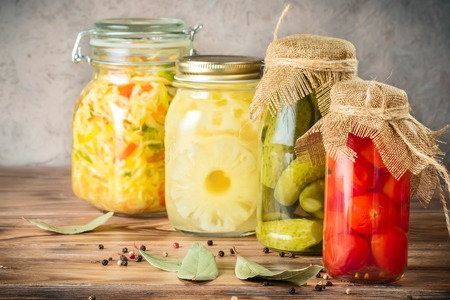 Set of fermented vegetables in jars on wooden rustic table. Cabbage salad sauerkraut pickled cucumbers cherry tomatoes and canned pineapples. Concept trend diet food vegetarian recipes to homemade