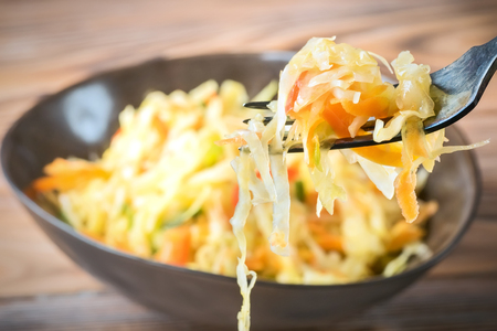 Salad appetizer of fermented vegetables sauerkraut carrots and peppers in bowl and on fork. Concept trend diet food vegetarian recipes to homemade