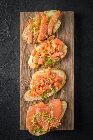 Bruschetta with sliced fish salmon, cucumber, arugula and young grass sprouts on a kitchen board for serving on black background with a copy space Imagens