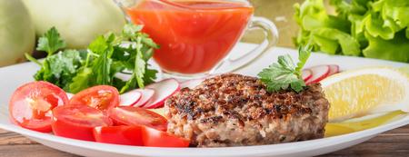 Chuleta de bistec picado cocido a la parrilla en un plato blanco con mezcla de verduras rábano tomates cherry rodajas de pepinos perejil limón y salsa de tomate Concepto de comida de verano barbacoa de picnic casera.