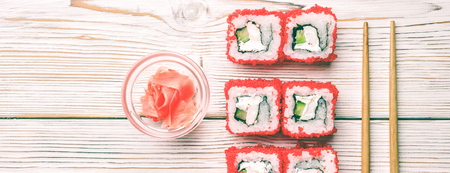 Set of sushi rolls of fresh shrimps cucumber avocado Tobiko caviar and Philadelphia cheese Asian food on white background with pickled fermented ginger and horseradish wasabi chopsticks. Stock Photo