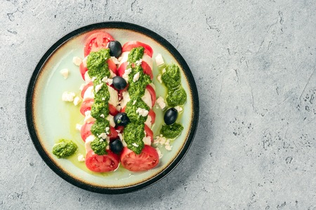 Tomato and mozzarella caprese salad and pesto sauce with olives on gray table. Food italian appetizer