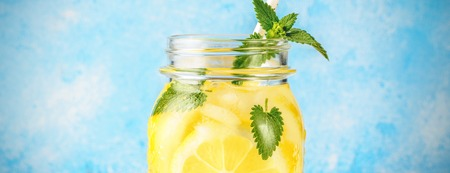 Coctail jar of lemonade and mint leaves on wooden table blue background Natural lemon water homemade food soda drink with fruit slices and drinking straw is popular detox beverage Glass of antioxidant infusion.