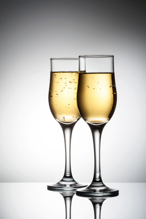 Two elegant glasses with sparkling champagne Holiday card Christmas, New Year, wedding. Celebration concept advertising design Banco de Imagens