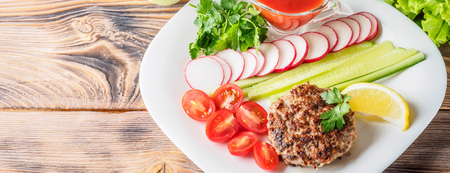 Chopped steak cutlet cooked on grill on white plate with assorty mix vegetables radish cherry tomatoes slices of cucumbers parsley lemon and sauce ketchup Concept food summer homemade picnic barbecue. Banco de Imagens