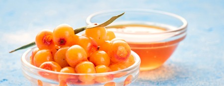 Sea-buckthorn berries in bowl and natural honey or sea buckthorn oil on blue background Concept of agriculture harvest healthy diet alternative medicine raising immunity in winter and autumn.