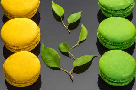 Colorful green yellow French sweet macaroons dessert cake macarons on dark background decorated with green leaves Banco de Imagens