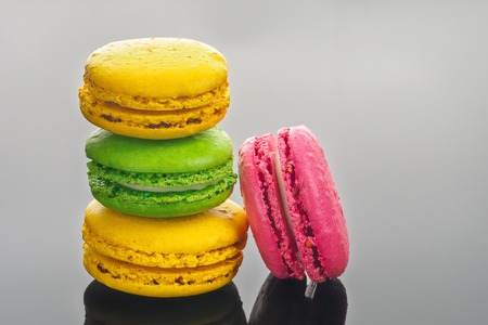 Colorful various French sweet macaroons dessert cake macarons on dark gray background copy space