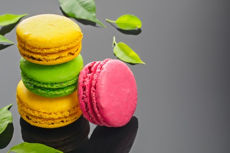 Colorful various French sweet macaroons dessert cake macarons on dark gray background decorated with green leaves copy space Banco de Imagens