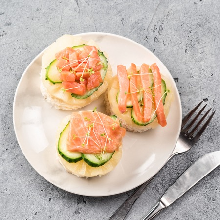 Bruschetta toast of white bread with slices of pineapple cucumber fish salmon and fresh green sprouts. Served on white plate on table fork with knife. Top view flat lay with copy space