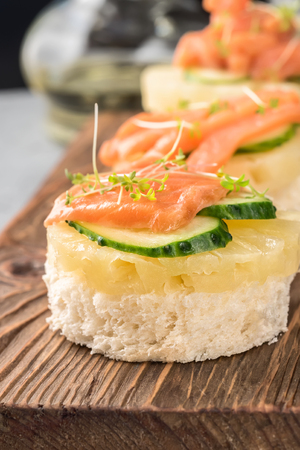Bruschetta toast of white bread with slices of pineapple cucumber fish salmon and fresh green sprouts. Served on wooden serving board table with apple juice, wine, olive oil