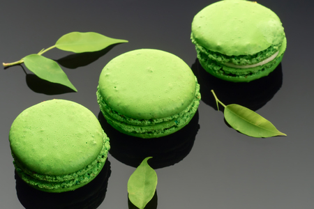 Colorful green yellow French sweet macaroons dessert cake macarons on dark background decorated with green leaves Standard-Bild