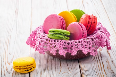 Assorted colorful sweet gentle soft French macaroons dessert cake macarons biscuit in bowl with knitted pink napkin on bright white table. Food concept Handmade recipe homemade Standard-Bild