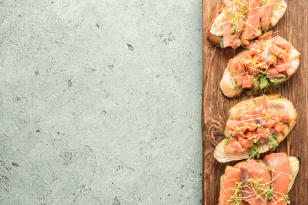 Bruschetta with sliced fish salmon, cucumber, arugula and young grass sprouts on a kitchen board for serving on gray background with a copy space
