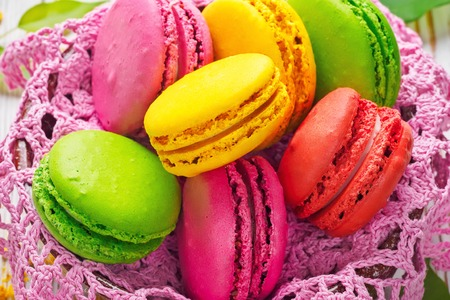 Assorted colorful sweet gentle soft French macaroons dessert cake macarons biscuit on knitted pink napkin. Food concept Handmade recipe homemade. Close-up macro