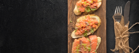 Bruschetta with sliced fish salmon, cucumber, arugula and young grass sprouts on a kitchen board for serving on black background served with a knife and fork with a copy space