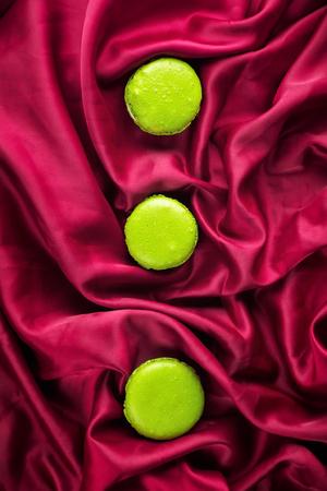 Green French sweet macaroons dessert cake macarons on red burgundy satin textiles background top view flat lay Standard-Bild