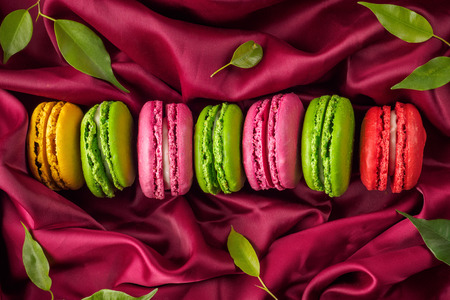 Colorful various French sweet macaroons dessert cake macarons on red burgundy satin textiles background decorated with green leaves top view flat lay