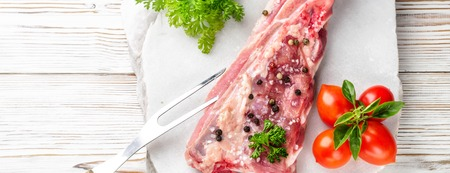 Piece of meat pork brisket ribs spatula seasoned with salt pepper cherry tomato and sprig of basil parsley on white wooden table marble stone served with fork food top view close-up with copy space.