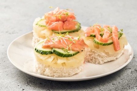 Bruschetta toast of white bread with slices of pineapple cucumber fish salmon and fresh green sprouts. Served on white plate on table. Top view flat lay with copy space Banco de Imagens