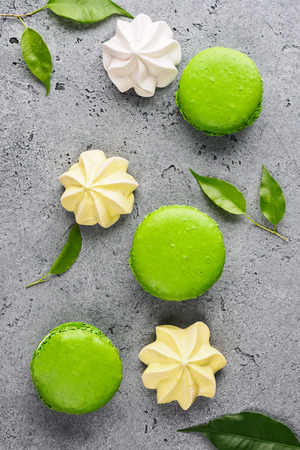 Green French sweet macaroons dessert cake macarons and pastel Meringue Marshmallow on gray background decorated with green leaves top view flat lay