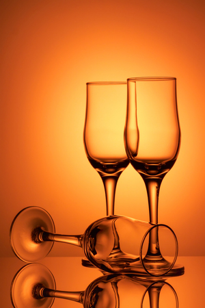 Three empty champagne glasses on colored background with reflection. Advertising image art toned Standard-Bild