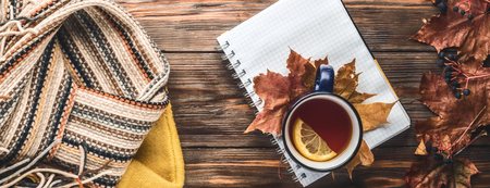 Autumn fashion seasonal concept yellow warm soft sweater Scandinavian knitted scarf cup hot black tea coffee Fall fallen maple leaves on wooden table with notebook pen. Flat lay Top view vintage style Banco de Imagens