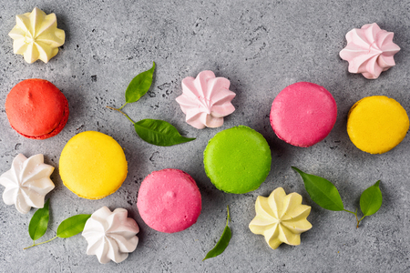 Colorful various French sweet macaroons dessert cake macarons and pastel Meringue Marshmallow on gray background decorated with green leaves top view flat lay