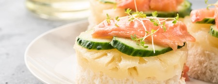 Bruschetta toast of white bread with slices of pineapple cucumber fish salmon and fresh green sprouts. Served on a white plate on table with mineral water olive oil