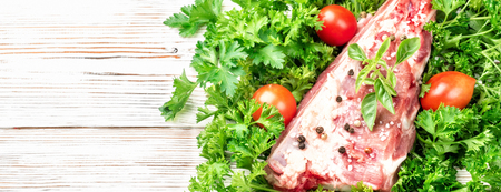 Piece of meat pork brisket ribs spatula seasoned with salt and pepper and sprig of basil on background fresh green parsley and cherry tomato food top view close-up with copy space. On wooden table Banco de Imagens