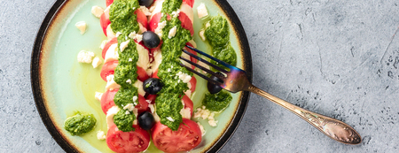 Tomato and mozzarella caprese salad and pesto sauce with olives on gray table served with fork. Food italian appetizer