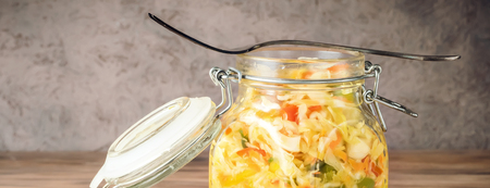 Salad appetizer of fermented vegetables sauerkraut carrots and peppers in glass jar with lid and fork on rustic wooden background. Concept trend diet food vegetarian recipes to homemade