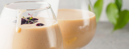 Two cocktail glass with smoothies milkshake healthy drink orange citrus peel bananas milk yogurt and ice cream with berries of black currant healthy diet food