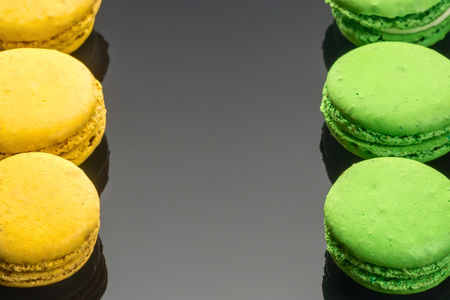 Colorful green yellow French sweet macaroons dessert cake macarons on dark backgrounds copy space