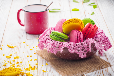 Assorted colorful sweet gentle soft French macaroons dessert cake macarons biscuit in bowl with knitted pink napkin on bright white table with red mug of tea and crumbled cake.