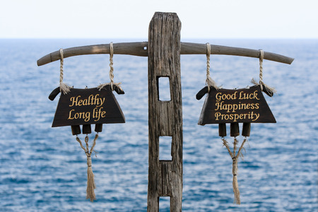 long life: Old wooden bell sign golden text to say healthy long life and good luck happiness prosperity against sea background.