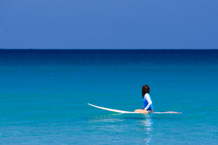 kata: Surfer girl sitting on surfboard in water at the beach. Kata Beach, Phuket, Thailand. Stock Photo