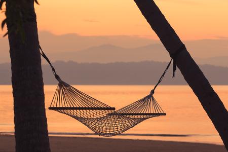 hamaca: hamaca de la tela contra la montaña y el mar al amanecer de fondo. Enfoque suave