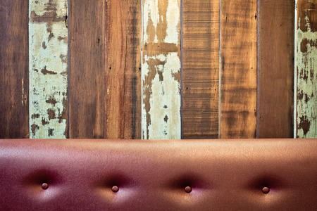 leather background: Vintage leather sofa with wood wall background.