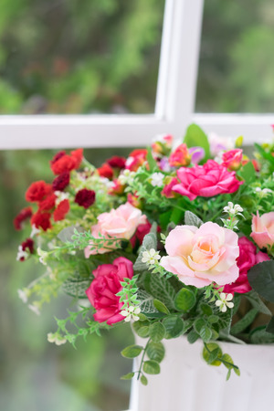artificial flower: Colorful decoration artificial flower against window background. Stock Photo