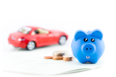 Piggy bank with car toy and coins isolated on white background.