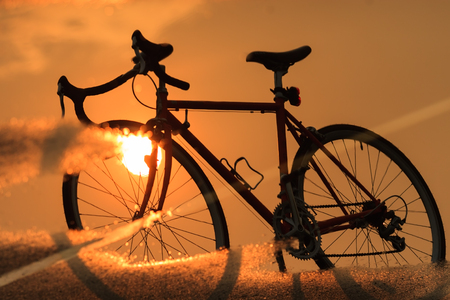 Silhouette of bicycle and reflection in the water against sunset.